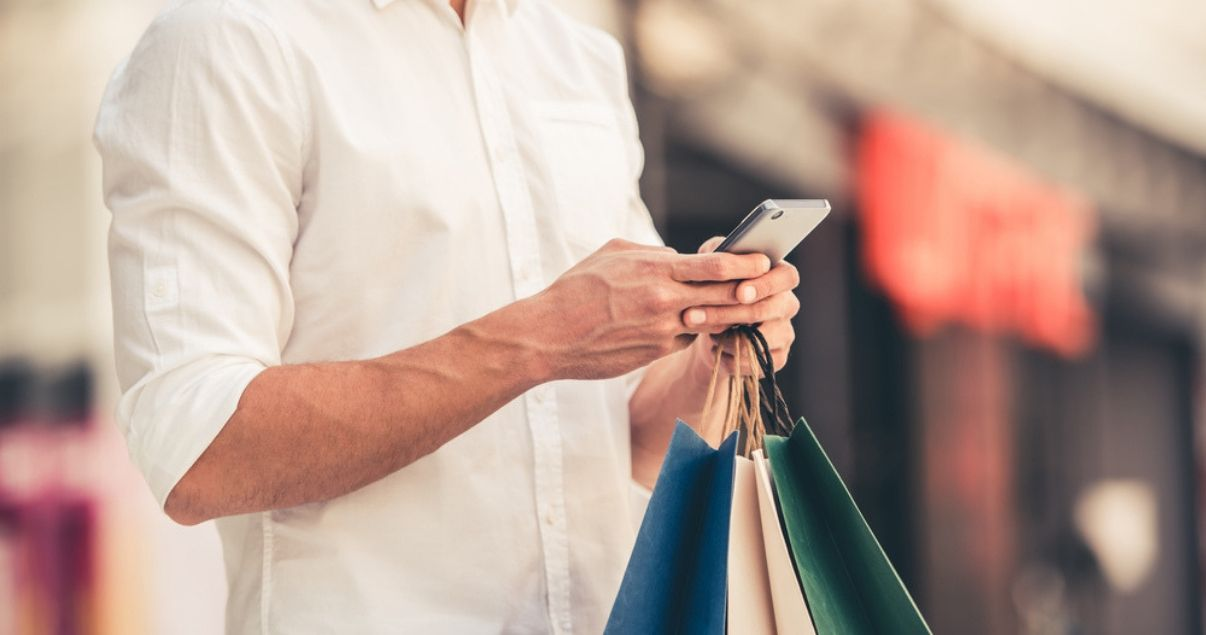 hombre de camisa amarilla sosteniendo bolsas y comprando en ecommerce en su celular