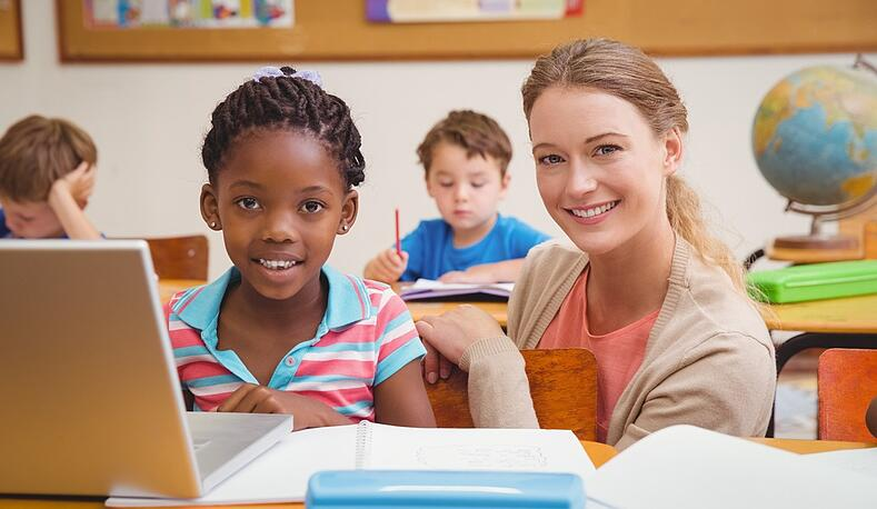 Cute pupil using computer with teacher at the elementary school.jpeg